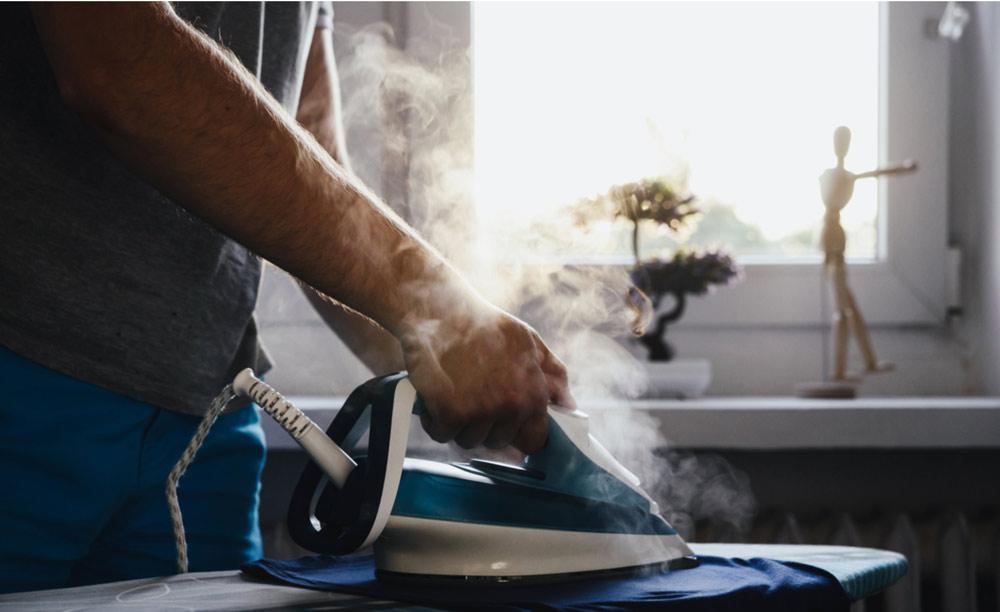 Homem passando roupas